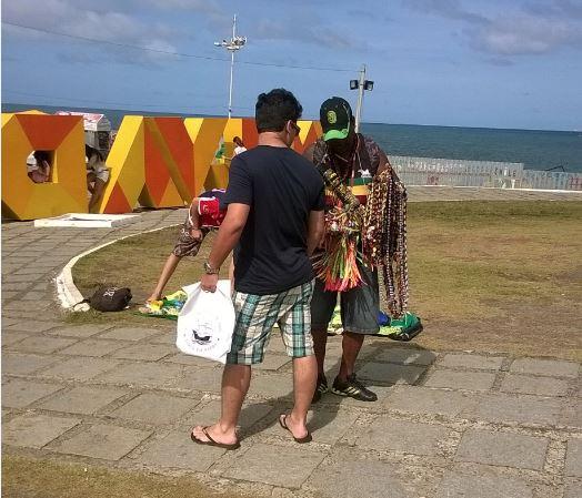 Vendedor aborda turista no Farol da Barra, em Salvador Foto de Aguirre Talento/Folhapress