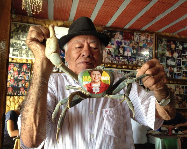 Luiz Moraes de Oliveira, o Luiz da Gia, 90, dono de restaurante, com seu guaiamum Bananeira, 3, mascote de Dilma em Goiana (PE) - Foto de Daniel Carvalho/Folhapress