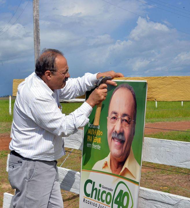 O governador Chico Rodrigues (PSB-RR) prega cartaz de sua campanha - Divulgação