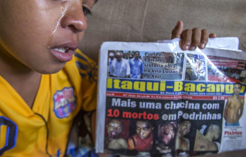 Fábio Henrique mostra jornal com pai baleado