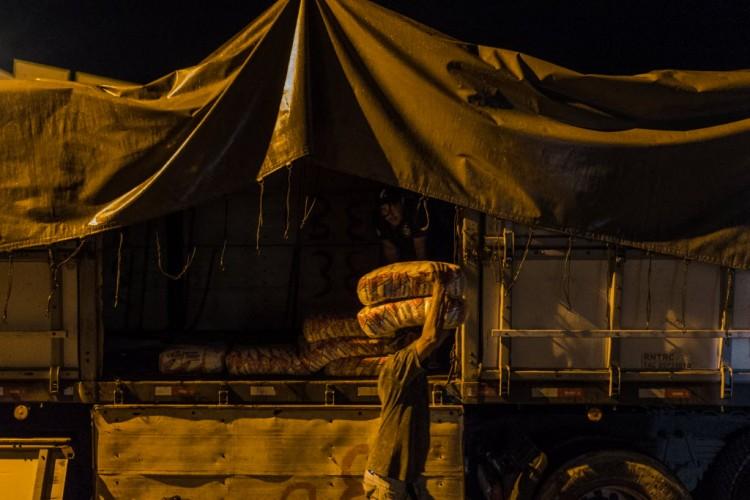 Trabalhadores descarregam carreta carregada de açúcar em comércio de Pacaraima (RR). Em meio a uma crise de abastecimento no seu país, centenas de venezuelanos estão atravessando a fronteira brasileira, em Roraima, atrás de comida e itens de necessidade básica - Avener Prado/Folhapress