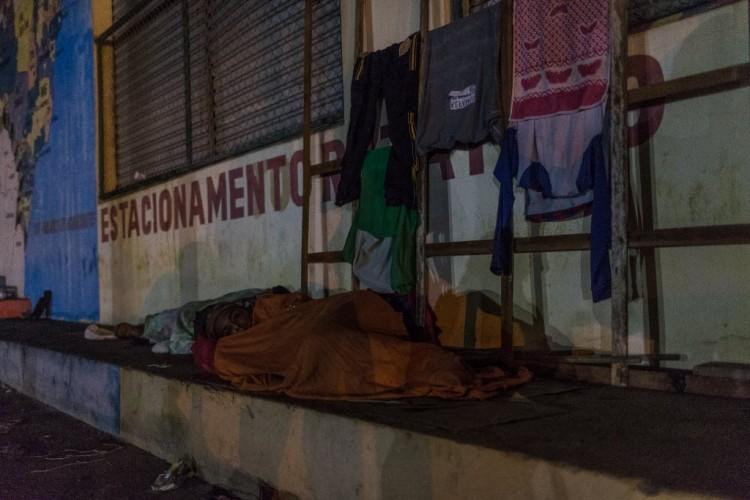 """Para economizar """"chapas"""" venezuelanos dormem nas ruas de Pacaraima enquanto aguardam caminhões para descarregar. Em meio a uma crise de abastecimento no seu país, centenas de venezuelanos estão atravessando a fronteira brasileira, em Roraima, atrás de comida e itens de necessidade básica. Em Pacaraima (RR), cidade fronteiriça de 12 mil habitantes, até lojas de material de construção e farmácias começaram a vender arroz, farinha, açúcar e óleo, para atender a alta demanda."""